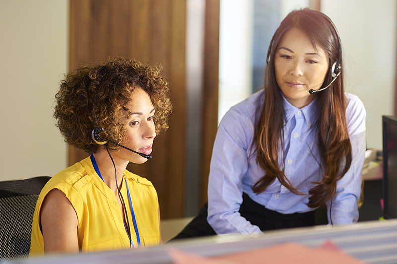 Health management services - a young call centre representative greets a caller in a large open plan office as her supervisor watches over her shoulder and helps her through the call.