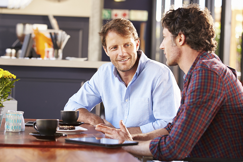 Two men sitting at a table in a cafe talking