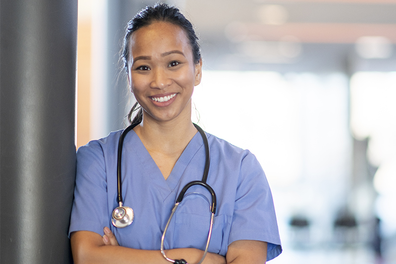 Nurse with a stethoscope leaning on a pole and smiling at the camera