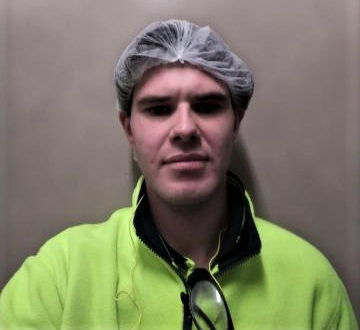 Man wearing high vis shirt with a hair net looking at camera