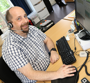 A man sitting at a computer wearing a headset and smiling at the camera